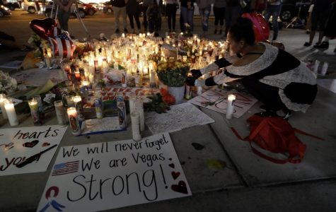 A woman places a candle at a memorial for victims of the mass shooting in Las Vegas.